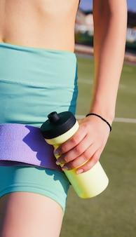 Une jeune femme est debout sur le terrain de sport. la fille tient un élastique de fitness et une bouteille d'eau dans ses mains. l'athlète s'est préparé pour la remise en forme.