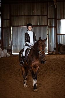 Jeune femme est engagée dans les sports équestres, la formation à cheval