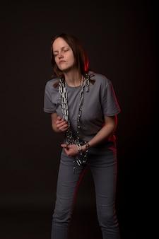 La jeune femme est liée à la chaîne, souffre de désespoir, de problèmes psychologiques. personne malheureuse avec concept de charge lourde.