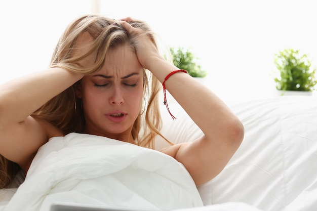 Jeune femme est malade rester au lit avoir un headacke