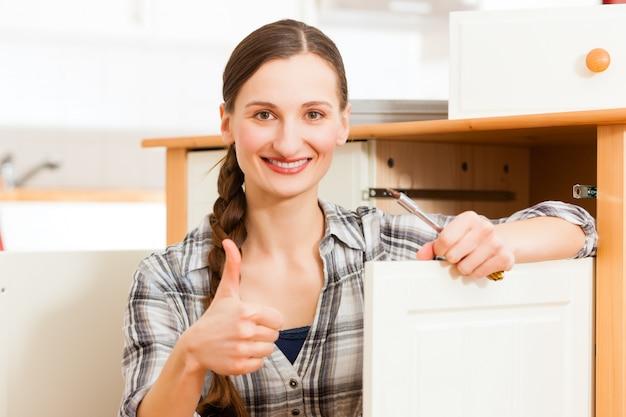Jeune femme est en train de monter un placard