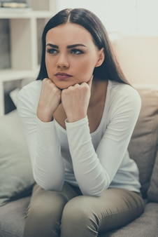 Jeune femme est tristement assise sur le canapé