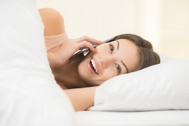 La jeune femme était allongée sur le lit et au téléphone
