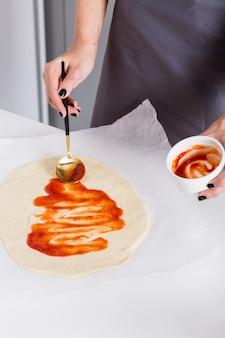 Jeune femme étalant la sauce tomate sur la pâte sur du papier sulfurisé
