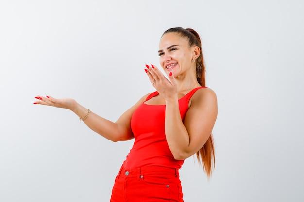 Jeune femme étend les paumes dans un geste désemparé en débardeur rouge, pantalon et à la joyeuse. vue de face.