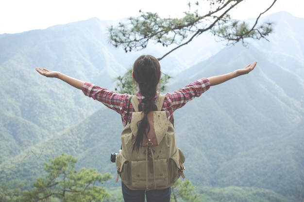 La jeune femme étendit ses bras au sommet de la colline dans une forêt tropicale avec des sacs à dos dans la forêt. aventure, randonnée.