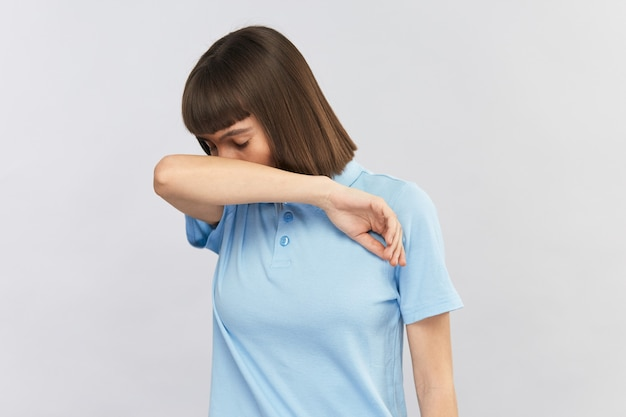 Jeune femme éternuant à son coude et couvrant son visage isolé sur un espace de copie gris, distance sociale et soins personnels, symptômes du virus.
