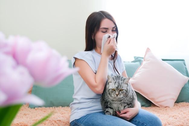 Une jeune femme éternue d'une allergie à la fourrure sur le canapé et joue avec son chat.