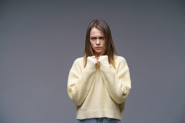 Une jeune femme d'ethnie caucasienne très énervée dans un pull jaune sur fond gris tient sa c...