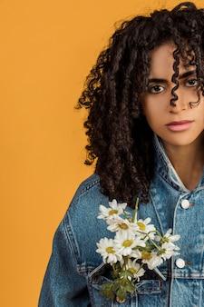 Jeune femme ethnique avec des fleurs sur une veste en jean