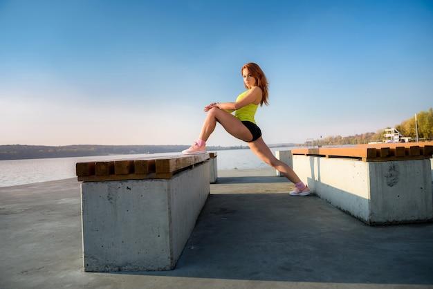 Jeune femme étirant les jambes tôt le matin avant le temps de travail à l'extérieur.