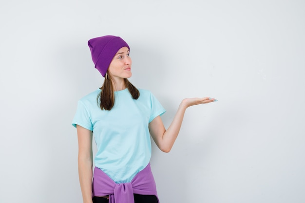 Jeune femme étirant la main comme affichant quelque chose et le regardant en t-shirt bleu, bonnet violet et semblant joyeux, vue de face.