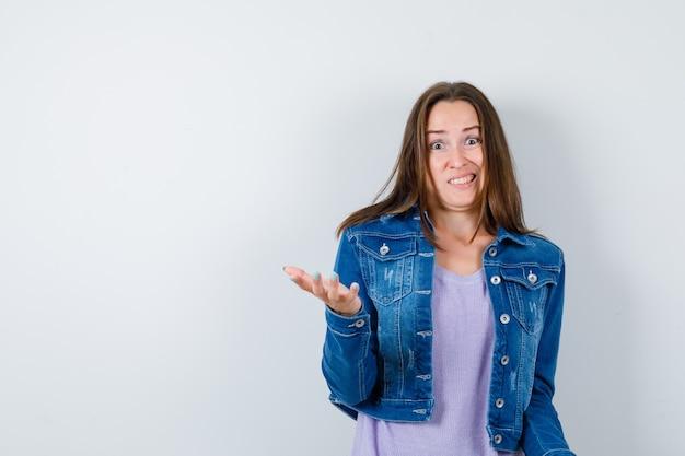 Jeune femme étirant la main dans un geste perplexe en t-shirt, veste et semblant agitée. vue de face.