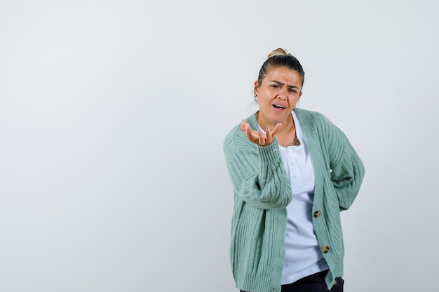 Jeune femme étirant les mains comme tenant quelque chose tout en gardant la main sur la taille en t-shirt blanc et cardigan vert menthe et l'air concentré