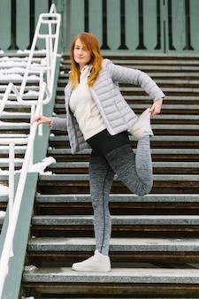 Jeune femme, étirement, elle, jambe, debout, gradins