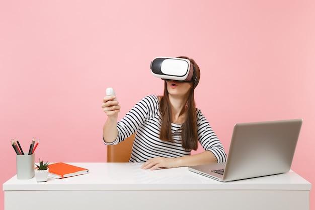 Jeune femme étonnée dans un casque de réalité virtuelle sur la tête à l'aide de la télécommande s'asseoir au bureau blanc avec un ordinateur portable isolé sur fond rose pastel. concept de carrière d'entreprise de réalisation. espace de copie.