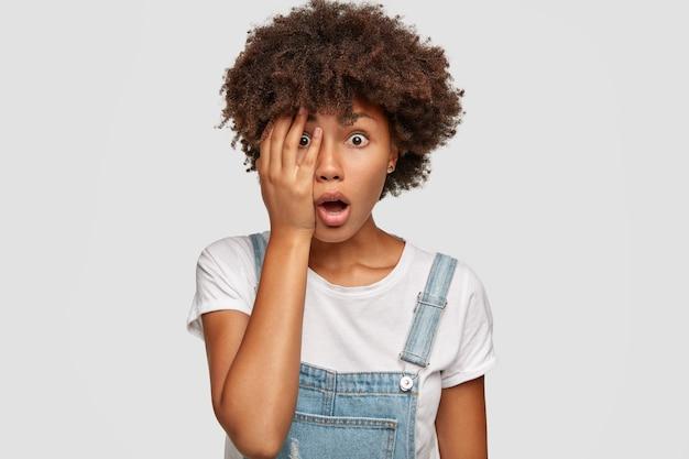 Une jeune femme étonnée à la peau sombre couvre le visage et ouvre la bouche avec étonnement