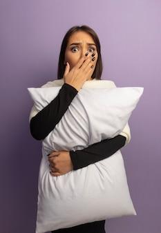 Jeune femme étreignant un oreiller choqué couvrant la bouche avec la main