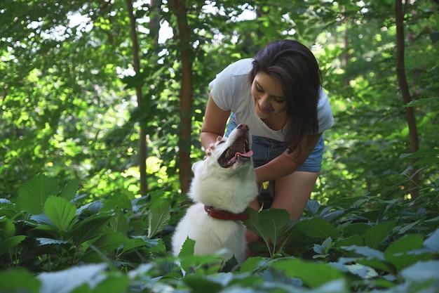 Jeune femme étreignant et tapotant son chien