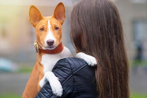 Jeune femme étreint son chien basenji terrier