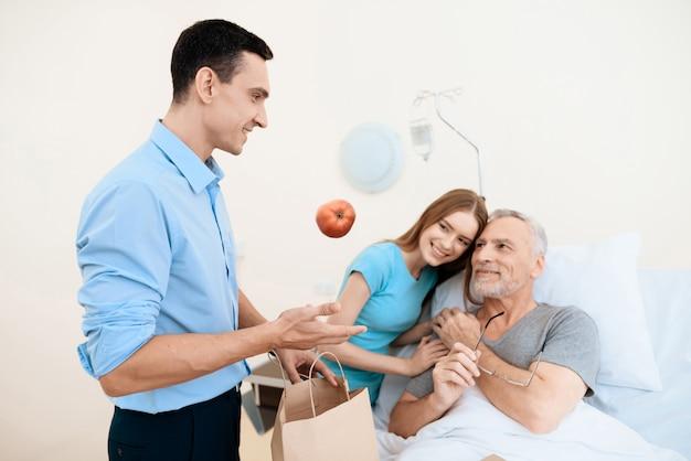 La jeune femme étreint le vieil homme.
