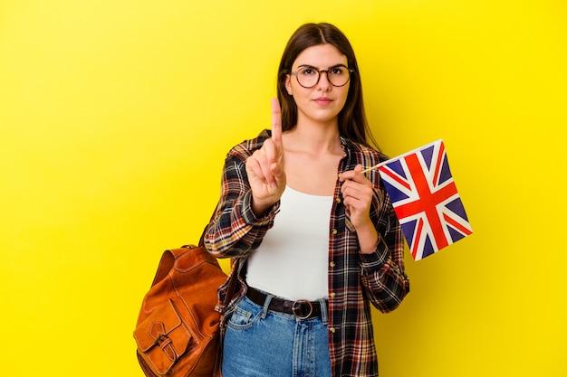 Jeune femme étudiant l'anglais isolé sur un mur rose montrant le numéro un avec le doigt.