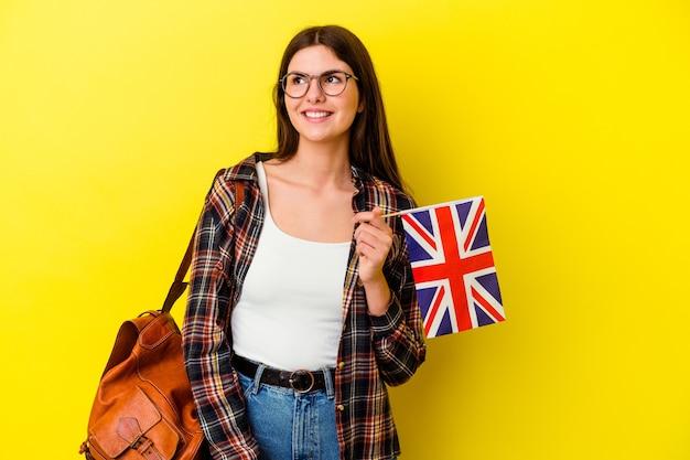 Jeune femme étudiant l'anglais isolé sur un mur rose regarde de côté souriant, gai et agréable.