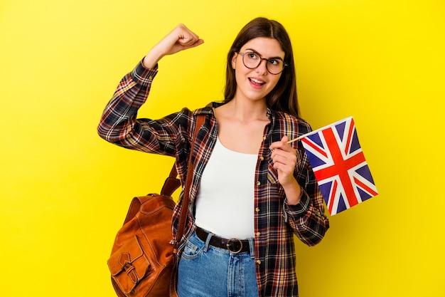 Jeune femme étudiant l'anglais sur le poing levé rose après une victoire, concept gagnant.