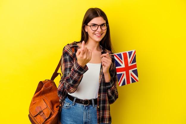 Jeune femme étudiant l'anglais sur rose pointant avec le doigt sur vous comme si vous invitiez à vous rapprocher.