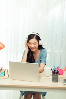 Jeune femme étudiant la navigation de l'ordinateur portable s'asseoir appel vidéo de bureau écouter leçon en ligne webinaire conférence éducation à distance sociale quarantaine à l'intérieur