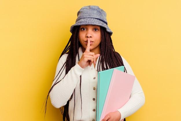 Jeune femme étudiante afro-américaine isolée sur fond jaune gardant un secret ou demandant le silence.
