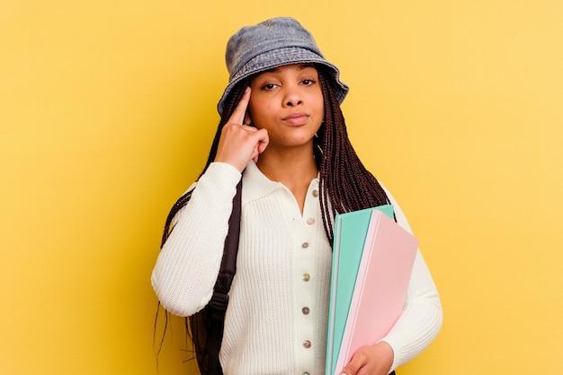 Jeune femme étudiante afro-américaine isolée sur le mur jaune pointant le temple avec le doigt, pensant, concentré sur une tâche.