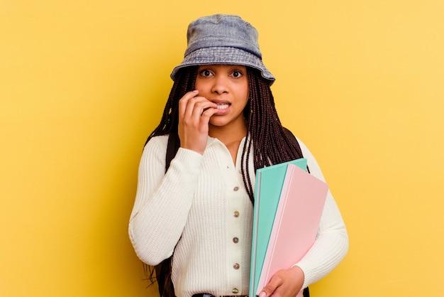 Jeune femme étudiante afro-américaine isolée sur mur jaune se mordant les ongles, nerveuse et très anxieuse.