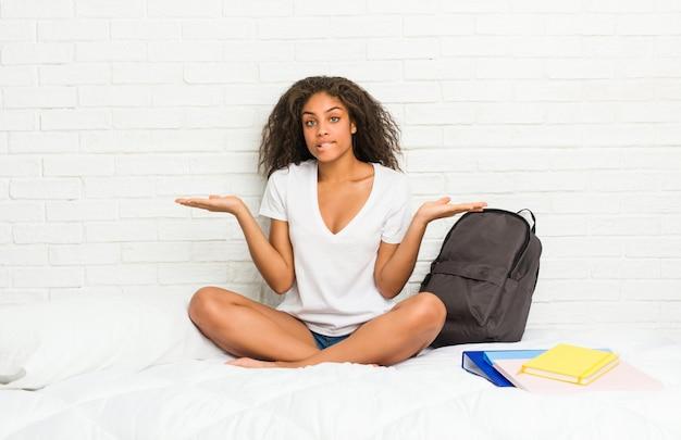 Jeune femme étudiante afro-américaine sur le lit confus et doutant haussant les épaules pour tenir un espace de copie.