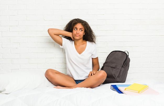 Jeune femme étudiante afro-américaine sur le lit, toucher l'arrière de la tête, penser et faire un choix.