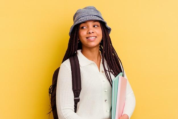 Jeune femme étudiante afro-américaine regarde de côté souriant, gai et agréable.