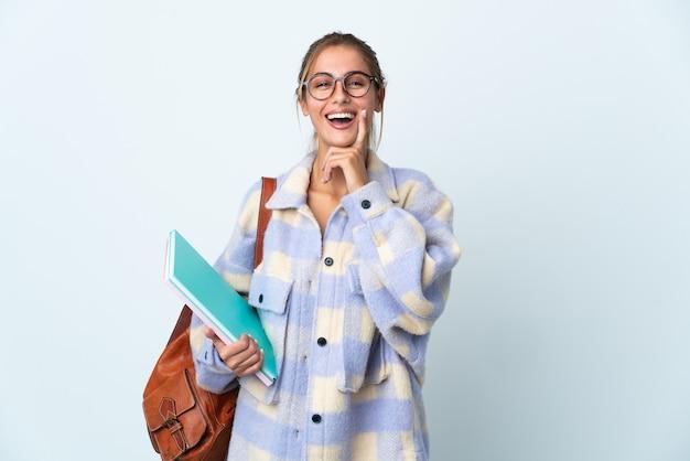 Jeune femme étudiante sur blanc souriant avec une expression heureuse et agréable