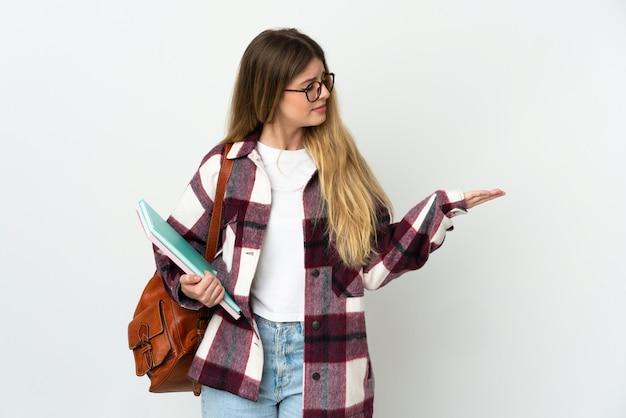 Jeune femme étudiante blonde isolée sur un mur blanc tenant copyspace avec des doutes