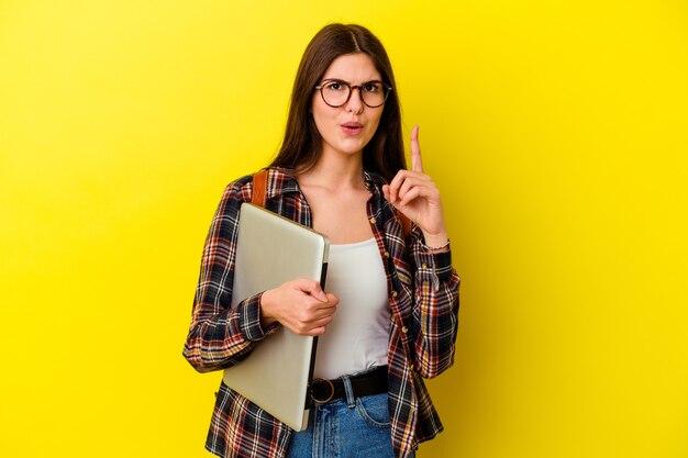 Jeune femme étudiante caucasienne tenant un ordinateur portable isolé sur fond rose ayant une excellente idée, concept de créativité.