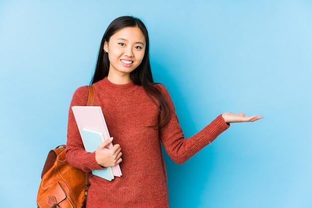 Jeune femme étudiante chinoise isolée montrant un espace de copie sur une paume et tenant une autre main sur la taille.