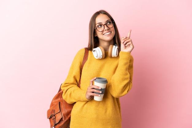 Jeune femme étudiante sur fond rose isolé pointant vers le haut une excellente idée