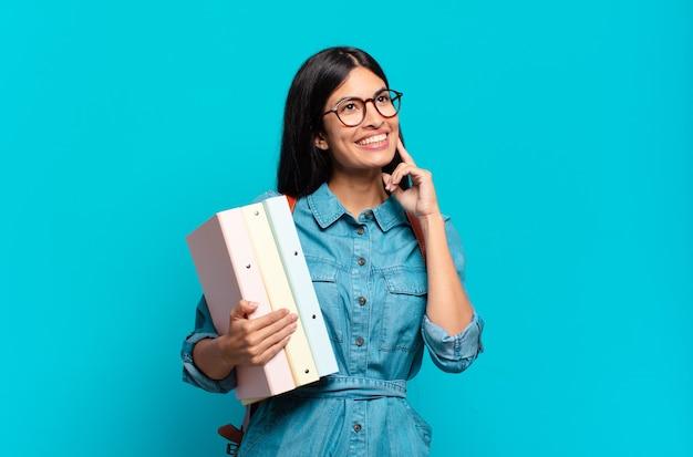 Jeune femme étudiante hispanique souriant joyeusement et rêvassant ou doutant, regardant sur le côté