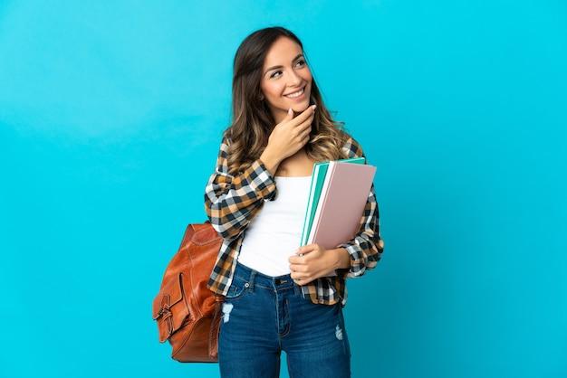 Jeune femme étudiante isolée sur un mur bleu en regardant en souriant