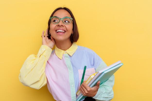 Jeune femme étudiante métisse isolée sur fond jaune essayant d'écouter un potin.