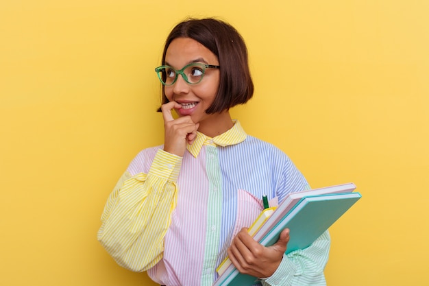 Jeune femme étudiante métisse isolée sur fond jaune pensée détendue sur quelque chose en regardant un espace de copie.
