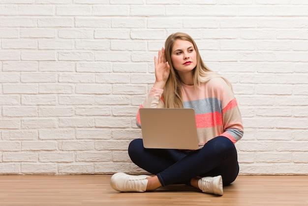 Jeune femme étudiante russe assise essayant d'écouter un commérage
