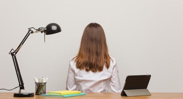 Jeune femme étudiante travaillant sur son bureau par derrière, regardant en arrière