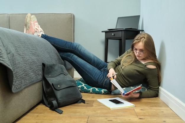 Jeune femme étudiante à l'université assis à la maison sur le sol et étudie à l'aide de livres