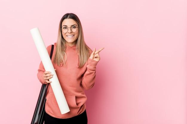 Jeune femme étudie l'architecture en souriant et en pointant de côté, montrant quelque chose à l'espace vide.