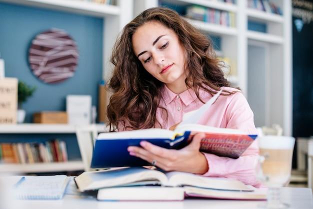 Jeune femme étudie dans la bibliothèque
